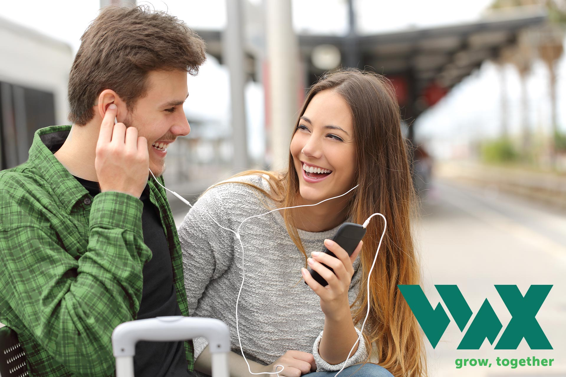Wax: A couple shares ear phones to listen to music on their phone.